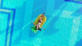 Eine Person steht in einem Pool still und schwimmt auf eine Gummimatratze Sorglose Dame in einem Pool stock video