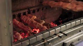 Eine Person stellt Aufsteckspindeln mit Fleisch auf einem Messingarbeiter mit brennenden Kohlen ein stock video