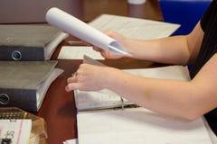 Eine Person, welche auf dem Tisch die Dokumente im Wohnzimmer ansieht, können Sie Hände und Dokumente sehen Lizenzfreies Stockbild