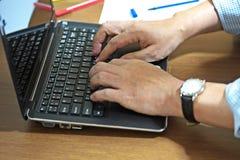 Eine Personenarbeit über Schreibtisch Lizenzfreies Stockbild