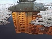 Eine Pfütze, in der Oberfläche des Wassers eine Reflexion eines hohen Wohnhauses, beleuchtete durch die orange Strahlen der unter Stockfotografie