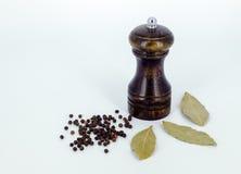 Eine Pfeffermühle mit Körnern des schwarzen Pfeffers im weißen Hintergrund Lizenzfreie Stockfotografie