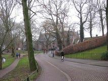 Eine Pflasterstraße mit Radfahrer durch einen Park in Utrecht, die Niederlande stockfotografie