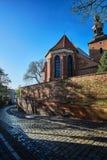Eine Pflasterstraße, eine mittelalterliche Wand und eine gotische Kirche Lizenzfreies Stockfoto