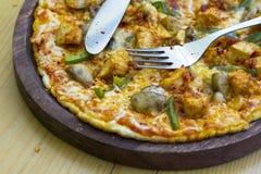 Eine Pizza-Scheibe in der Platte, in den Gabeln und im Messer Lizenzfreie Stockfotos