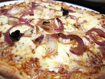 Eine Pizzeria, überstiegen mit Schinken und Käse Lizenzfreie Stockfotografie