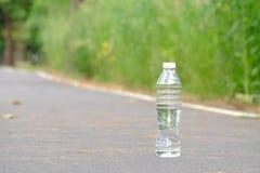 Eine Plastikflasche Trinkwasser verunreinigend auf dem Straßenpark mit grünem Naturhintergrund für ein Klimareinigungskonzept stockfotografie