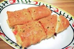 Eine Platte der Pizza rollt mit Schinken und Käse Lizenzfreie Stockfotos