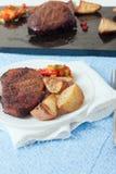 Eine Platte des Steaks, der gebratenen Kartoffeln und der Pfeffer Stockbild