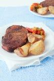Eine Platte des Steaks, der gebratenen Kartoffeln und der Pfeffer Lizenzfreies Stockbild