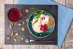 Eine Platte des Vanilleeises mit Blume, Beeren und Gewürzen Ein kalter Snack und ein Glas Saft auf einem hölzernen Hintergrund Lizenzfreie Stockbilder