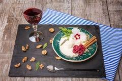 Eine Platte des Vanilleeises mit Blume, Beeren und Gewürzen Ein kalter Snack und ein Glas Saft auf einem hölzernen Hintergrund Lizenzfreie Stockfotos