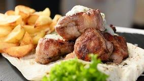 Eine Platte mit bereit-gebratenem Fleisch, gewürzt mit Zwiebeln und gebratenen Kartoffeln stock footage