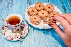 Eine Platte mit einem Keksplätzchen und einer Schale schwarzem Tee mit Stücken Zucker auf einem blauen hölzernen Hintergrund Lizenzfreie Stockbilder