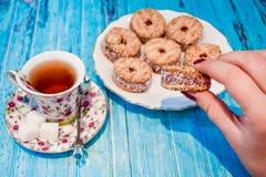 Eine Platte mit einem Keksplätzchen und einer Schale schwarzem Tee mit Stücken Zucker auf einem blauen hölzernen Hintergrund Lizenzfreies Stockbild
