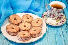 Eine Platte mit einem Keksplätzchen und einer Schale schwarzem Tee mit Stücken Zucker auf einem blauen hölzernen Hintergrund Lizenzfreies Stockfoto