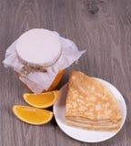 Eine Platte mit Pfannkuchen auf einem h?lzernen Hintergrund nahe bei orange Scheiben und einem Glas bedeckt mit Wachspapier und F lizenzfreie stockbilder