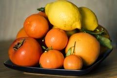 Eine Platte mit Zitrusfrüchten und persommons Stockbild