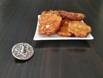 Eine Platte voll von hannukah Kartoffel Latkesstückchen mit einem silbernen dreidel auf einem Holztisch Stockbilder