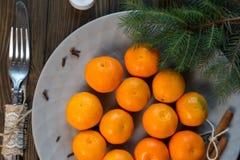 Eine Platte von Tangerinen bleiben auf dem Holztisch lizenzfreie stockfotografie