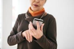 Eine positive moderne ältere Frau hält einen Handy und benutzt ihn Die ältere Generation und die moderne Technologie lizenzfreie stockfotografie