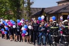 Eine Prozession von Studenten des Rettungsdiensts und der Feuerwehrmänner Feiern Mai erster, der Tag des Frühlinges und Stockbilder