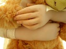 Eine Puppe, die einen Teddybären hält Stockfotografie