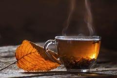 Eine rauchige Schale mit Tee und ein rotes trockenes Blatt auf einem dunklen Hintergrund Stockfotografie