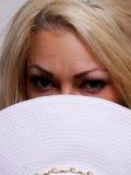 Eine recht blonde Frau, die über ihrem Hut schaut Lizenzfreies Stockfoto