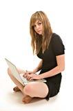 Eine recht junge Frau, die an einem Laptop arbeitet Lizenzfreie Stockfotografie
