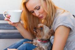 Eine recht kaukasische Frau zu Hause, die auf dem Portal mit Hund sitzt Stockfotos