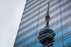Eine Reflexion eines Leuchtfeuerturms auf einem modernen Gebäude stockfotos