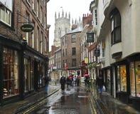 Eine regnerische niedrige Petergate Szene, York, England Stockbild