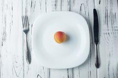 Eine reife Aprikose auf einer leeren weißen Platte Lizenzfreies Stockfoto