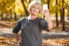 Eine reife Frau in einem Kleid macht selfie im Park Stockbild