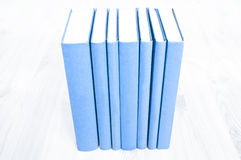 Alte blaue Bücher auf hölzernem Schreibtisch Stockbild