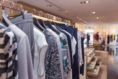 Eine Reihe der Kleidung, die an den Aufhängern im Speicher hängt Lizenzfreie Stockbilder