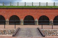 Eine Reihe geschlossene alte Tore in einer Backsteinmauer Lizenzfreie Stockfotos