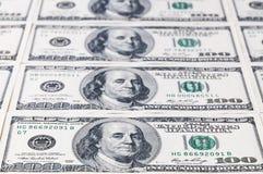 Eine Reihe Hundertdollar-Banknoten, die im Abstand verlassen Fokus auf der ersten Banknote Stockfotos