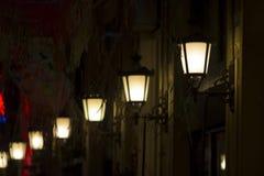 Eine Reihe Retro- elektrische Lampen auf historischer errichtender Fassade, den Rahmen diagonal schneiden lizenzfreies stockbild