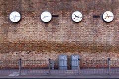 Eine Reihe Uhren, welche die Zeiten in den bedeutenden Städten registrieren Lizenzfreie Stockbilder