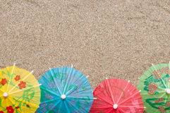 Eine Reihe von bunten kleinen Cocktailregenschirmen auf Meersand Lizenzfreie Stockfotografie