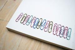 Eine Reihe von Clipn auf einem Notizbuch Lizenzfreie Stockfotografie