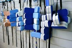 Eine Reihe von den Schwimmengurten, die an PVC-Bar durch Swimmingpool agai hängen Stockfotografie