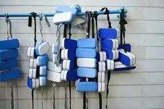 Eine Reihe von den Schwimmengurten, die an PVC-Bar durch Swimmingpool agai hängen Lizenzfreie Stockfotos