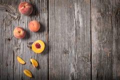 Eine Reihe von frisch ausgewählten ganzen und geschnittenen Pfirsichen auf einem hölzernen Hintergrund stockbilder