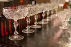 Eine Reihe von Glaswaren des geschliffenen Kristalls auf einer schwarzen Tischplatte Stockfotos