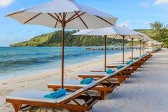 Eine Reihe von sunbeds und von Tüchern an einem Strandurlaubsort Stockbilder