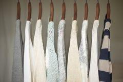Eine Reihe von warmen und weichen Strickjacken für Frauen auf hölzernen Aufhängern Stockfotos
