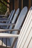 Eine Reihe von weißen Adirondack-Stühlen Lizenzfreie Stockbilder